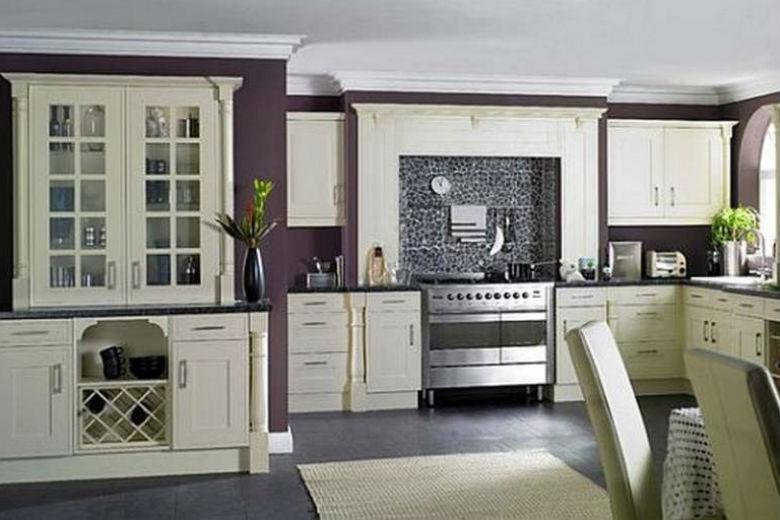 Fioletowa ściana w kuchni jest dobrym tłem dla białych mebli