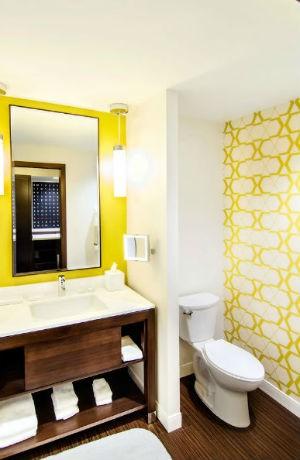 Żółta ściana wokół lustra w łazience, fot. Chros Bradley Photography