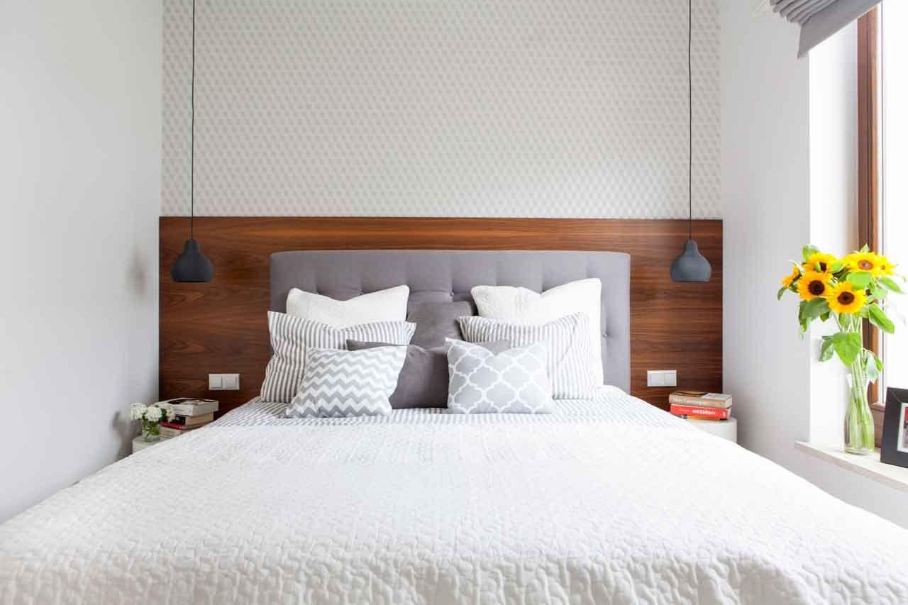Przytulny nastrój w tej sypialni tworzy drewno orzecha o ciepłej barwie, którym wyłożono ścianę za łóżkiem, a także miękkie tekstylia - tapicerowany zagłówek łóżka i leżące na nim pod
